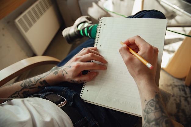 Chiuda su delle mani del maschio che scrivono su un concetto vuoto della carta, di istruzione e di affari
