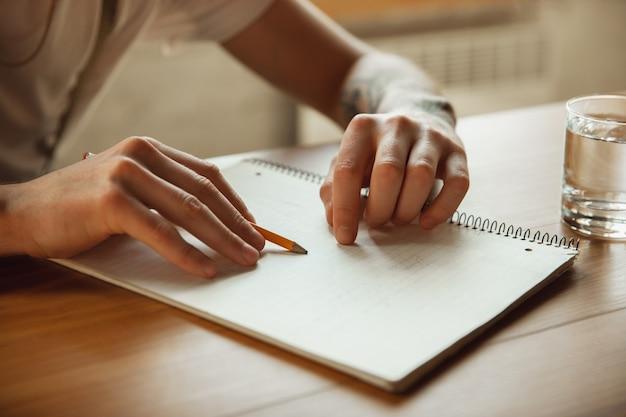 Primo piano di mani maschili che scrivono su un foglio vuoto sul tavolo di casa. prendere appunti, casa di lavoro, relazione per il suo lavoro. istruzione, freelance, arte e concetto di business. lascia la firma, facendo scartoffie.