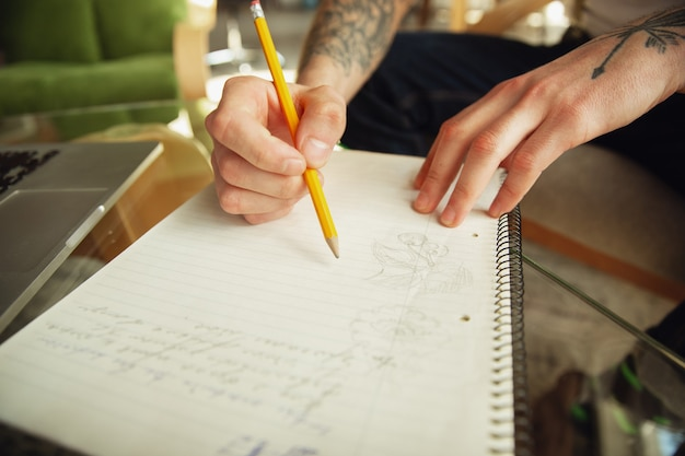 Close up of male hands writing on an empty paper on the table at home. making notes, workhome, report for his work. education, freelance, art and business concept. leaves signature, doing paperwork.