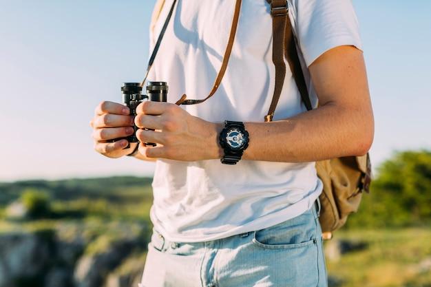 Primo piano della viandante maschio che tiene binoculare in sua mano
