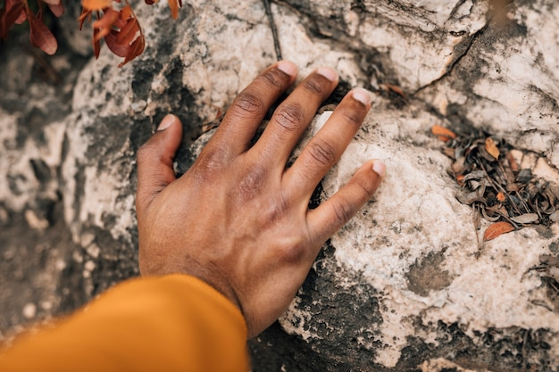 Close-up of male hiker's hand touching the rock