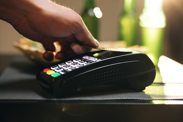 Close up of male hold in hand wireless modern bank payment terminal