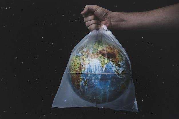 黒の背景にビニール袋地球世界地球儀で男性のホールドを閉じます。惑星を救ってください、惑星はプラスチックで窒息しています..自然のゴミ、エコロジー環境保護の概念を止めてください。スペースをコピーします。