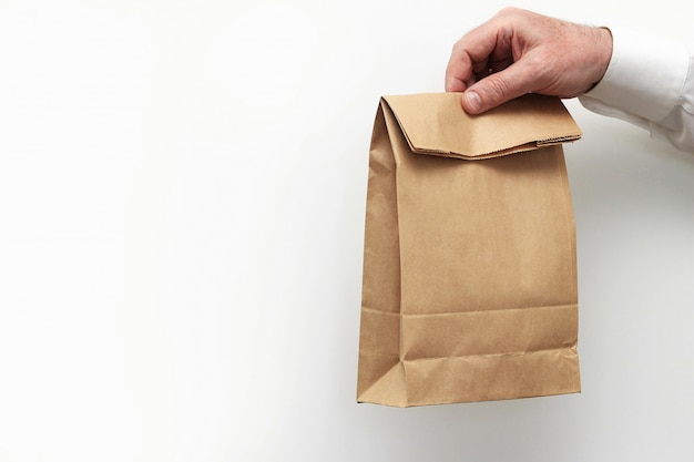 Close up male holds in hand clear empty blank craft paper bag for takeaway
