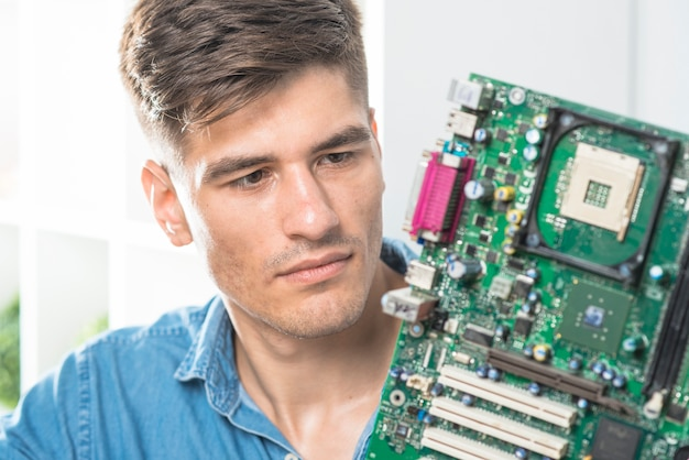 Close-up of male it technician looking at motherboard