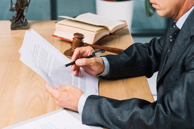 Close-up of male lawyer holding pen reading document at wooden desk