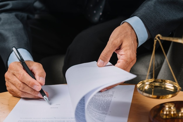 Close-up of male lawyer signing the contract document on the desk