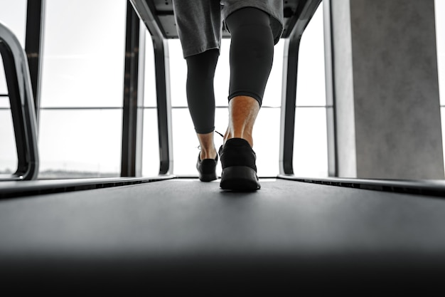 Close up of male legs running in a gym on a treadmill
