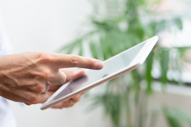 Close-up of male manager showing online data while using tablet