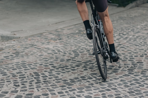 Close up of male muscular legs riding bike on road