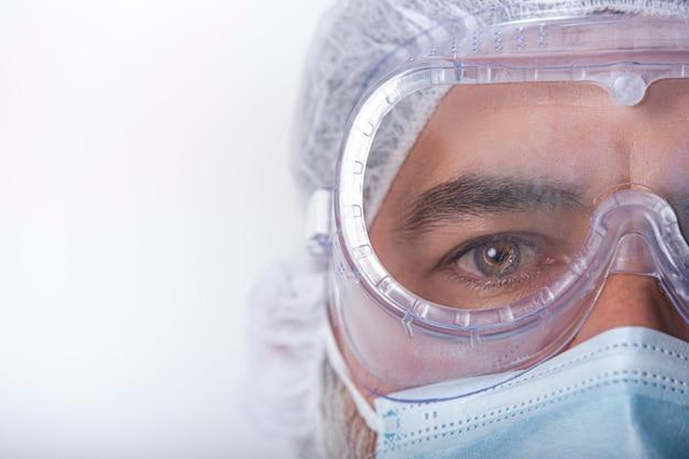 コロナウイルスのパンデミック時にマスクを着用し、安全メガネ、手袋を着用している男性看護師をクローズアップします。テキスト用のスペース