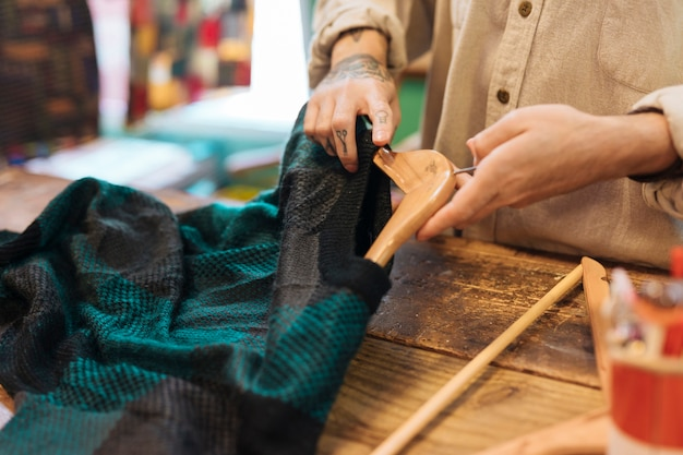 Close-up of a male owner arranging clothes on hanger
