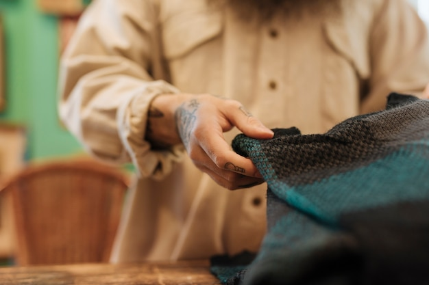 Close-up of a male owner folding the sweat shirt