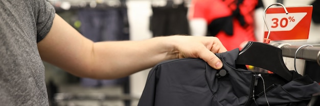 Close-up of male person choosing black casual jacket in shopping centre.