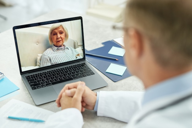 Close up of male physician sitting at the table with laptop and talking with elderly lady through video call