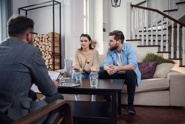 Close up of male psychologist sits at chair and listens depressed young couple at stylish cozy office. selective focus.