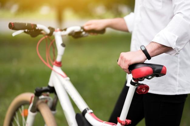 Крупным планом мужчина готов кататься на велосипеде на открытом воздухе