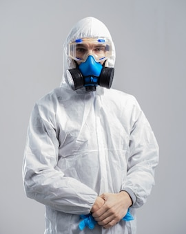 閉じる。防護服と抗ウイルスマスクを着用した男性用消毒剤。