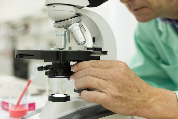 Close-up of a male scientific researcher using microscope in the laboratory.