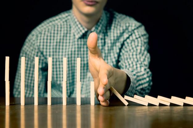 暗い背景のテーブルに手で男性ストップドミノ落下をクローズアップf