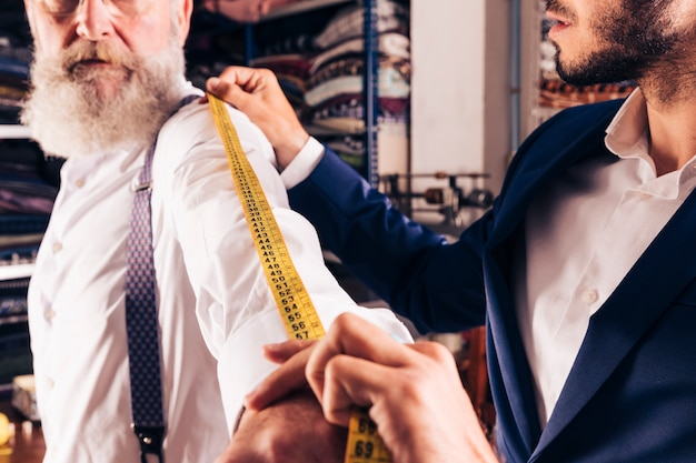 Close-up of male tailor taking measurement of senior man's sleeves