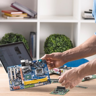 Close-up of male technician holding modern computer motherboard from table