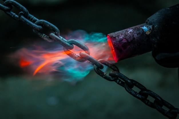 Мужской сварщик крупным планом сваривает металл с помощью газовой горелки. работник использует газовую горелку для металлических деталей в мастерской.