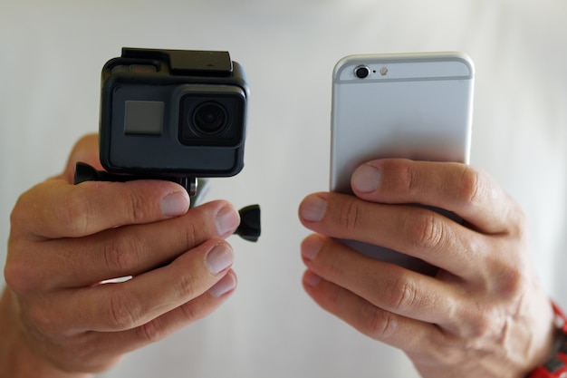 Close-up. male with action camera to smartphone wireless wifi connection.