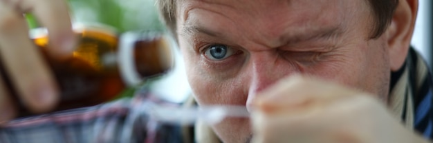 Close-up of males face carefully measuring cure from cough in spoon. middle-aged man wearing scarf around neck.