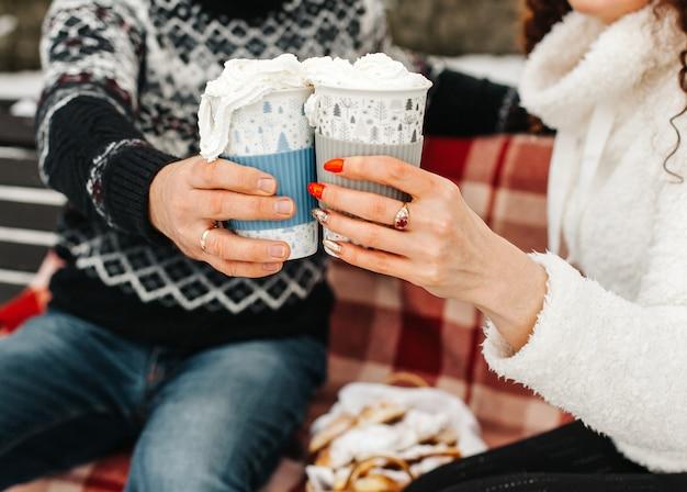 확대. 겨울 숲에서 크림과 함께 뜨거운 코코아 컵을 들고 있는 남자와 여자
