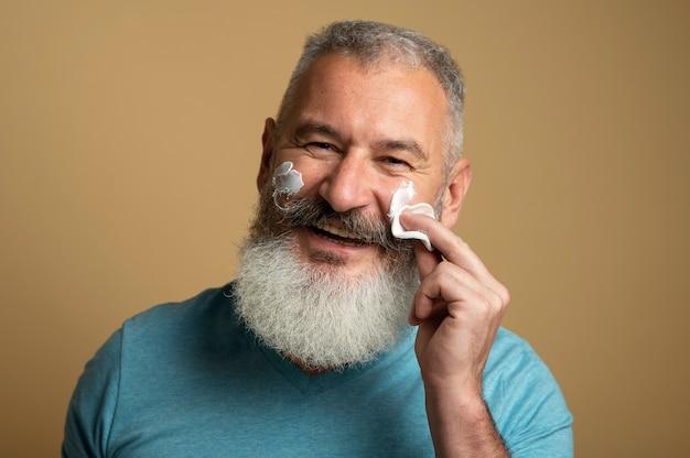 Uomo ravvicinato che applica la crema per il viso