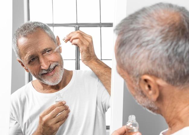 Uomo del primo piano che applica siero del viso