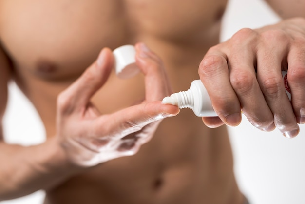 Close up man applying lotion on finger