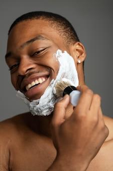 Primo piano uomo che applica crema da barba