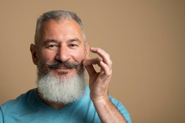 Close up man arranging moustache
