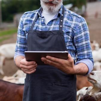 Крупным планом человек на ферме, глядя на планшет