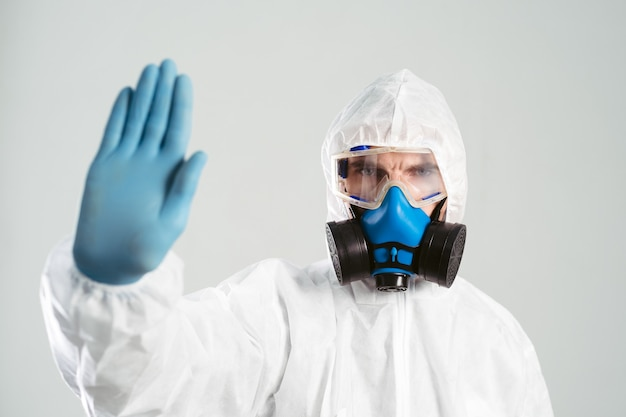 Close-up. man in a biohazard suit makes a stop sign. photo with a copy-space.