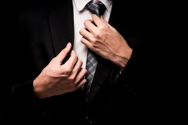 Close up of man in black suit, shirt and tie on black background