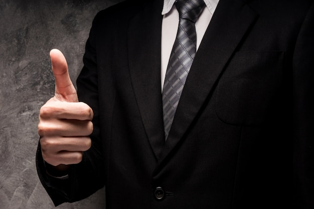 Close up of man in black suit with hand gesture on gray grunge background.