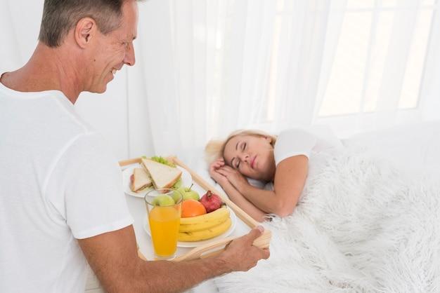 眠っている女性に朝食をもたらすクローズアップ男