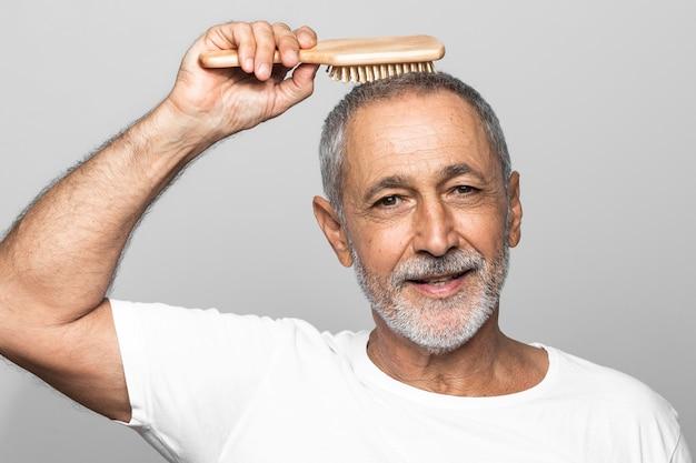 Uomo del primo piano che spazzola i suoi capelli