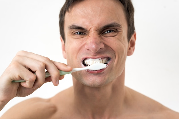 Close up man brushing teeth