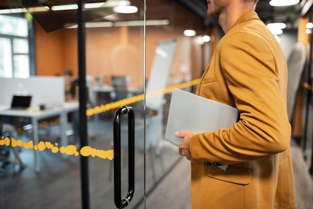 Крупным планом человек, несущий ноутбук