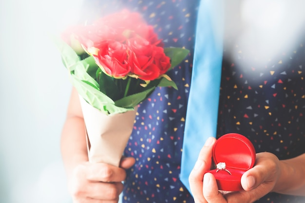 Close up man in casual shirt and necktie holding diamond ring and roses bouquet