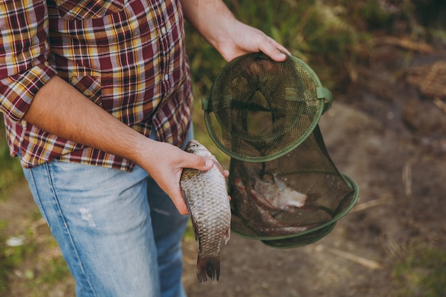 Primo piano l'uomo in camicia a scacchi con maniche arrotolate tiene in mano la griglia da pesca verde e il pesce che ha catturato sulla riva del lago vicino ad arbusti, canne. stile di vita, ricreazione, concetto di svago del pescatore
