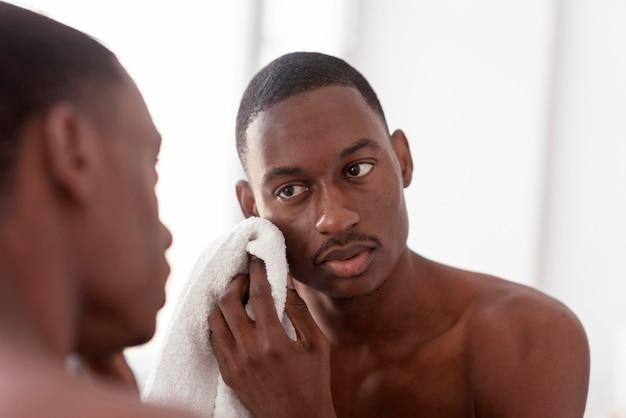 Chiuda sull'uomo che pulisce il suo fronte