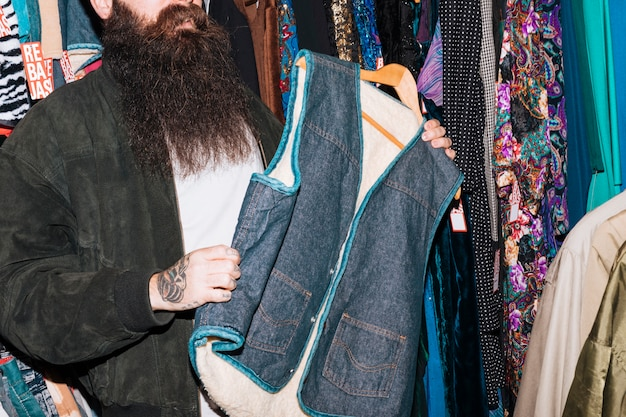 Close-up of a man in clothing store holding denim fur jacket in hand