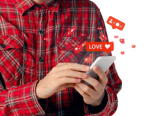 ガジェットを使用してソーシャルメディアに接続して共有している男性をクローズアップコメントを取得いいね!