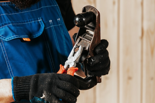 Close-up of a man construction worker adjusting a black old plane with pliers in a workshop