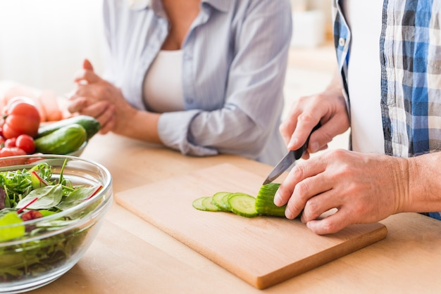 Close-up of man cutting the cucumber with knife on chopping board